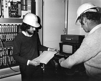 Tasman Pulp & Paper Co Ltd, Kawerau: 1982 P Murname and T Clayton carry out program change to wood preparation computer; 1982; Photograph