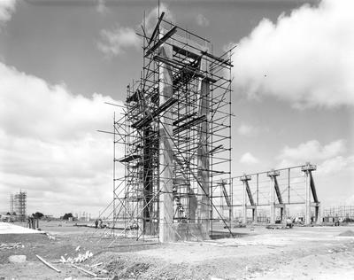 Fletcher Construction Co Ltd - Hangar and Workshop for TEAL, Auckland Airport, Mangere: 1964 under construction showing the right front and left hand front buttress