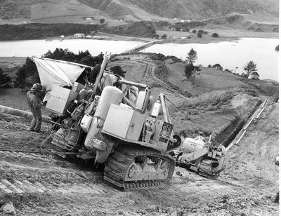 Fletcher Construction Co Ltd - Contracts - Kapuni Gas Pipeline, Taranaki to Auckland/Wellington: 1969 Close-up of machines laying pipeline on steep hill down to the Mokau River, King Country