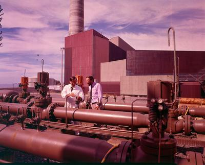 Fletcher Holdings Ltd: 1976 Gas control station with the massive power house as the backdrop at New Plymouth Power Station, Taranaki
