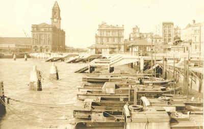 Winstone's relationship with Auckland City: 1917 Auckland waterfront with Ferry Building in background, small boat tied up at wharf