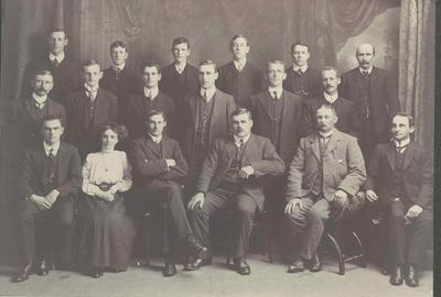 Wright Stephenson & Co Ltd - Gore Branch, Southland: 1911 staff - Back row W J H Wilson (Hardware Department); A Shivas (Sadler's Assistant); T Stevenson (delivery cart); J Simpson (clerk); T Hood (Grocer's Assistant); A Corbett (storeman); Middle row J C McPherson (clerk); G H Donaldson (clerk); M A O'Neill (Grocer's Assistant); J R Stevenson (Produce salesman), WD Shelton (clerk), PK Low (saddler). Front row - PC Mills (Ledger keeper); Miss Gilchrist (typist); R Nichol (Accountant); P C Gray (Manager); W N Woods (Auctioneer); G B Turnbull (Grocery Department);