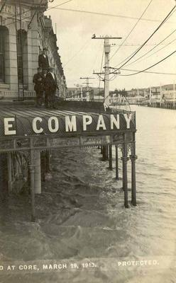 Wright Stephenson & Co Ltd - Gore Branch, Southland: Mar1913 Floods at Gore - corner of  main street, people standing on shop verandah roof