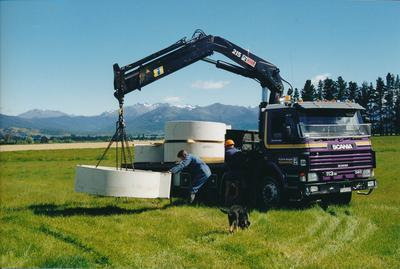 Hume Industries (NZ) Ltd - Hume Pipe Co: 1995 truck with crane lifting concrete rounds in rural setting