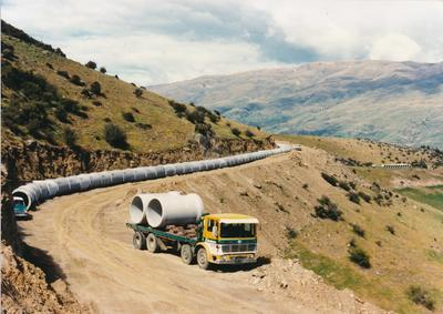 Hume Industries (NZ) Ltd - Hume Pipe Co: 1995 pipeline being laid in unknown location on hill country road; truck carrying pipes